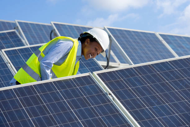 Energy engineer woman working on a roof with solar panels. Electrical engineer woman checking solar photovoltaic panels on the roof of a solar farm. power occupation stock pictures, royalty-free photos & images