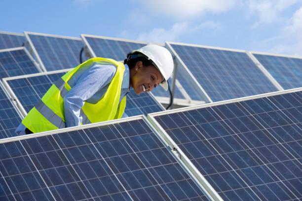 mujer ingeniero de energía trabajando en un techo con paneles solares. - energía solar fotografías e imágenes de stock