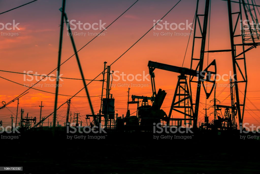 Energy extraction, crude oil recovery industry at sunset, blurred bacground stock photo