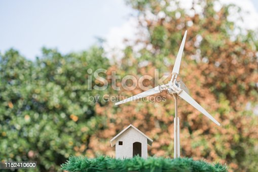 Energy future alternative, Power renewable /clean electric energy concept. Home / wind turbine that shows use of green energies on orage background. Alternative of nature or environmental conservation