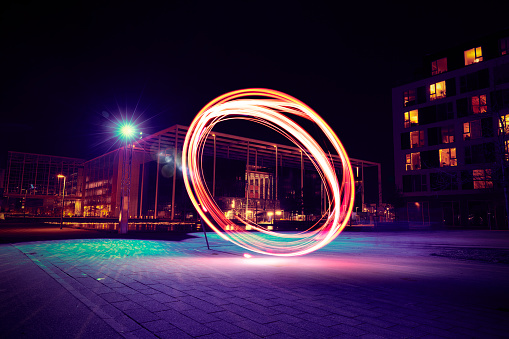 A bright red ring of clean energy in the middle of the city. It is night and the light is seen brightly