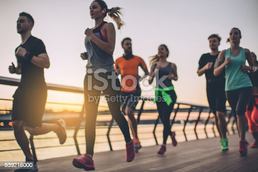 Group of young people competing in a race. Young men and women running on riverside promenade at sunset. They are wearing sport clothing.