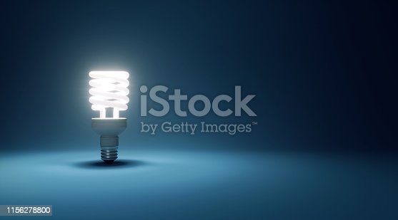 Energy saver light bulb glowing on dark cyan background. Horizontal composition with copy space.