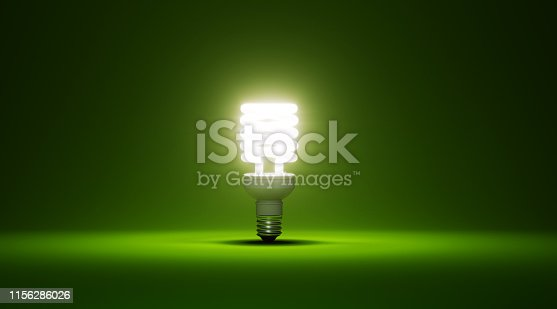 Energy saver light bulb glowing on green background. Horizontal composition with copy space.