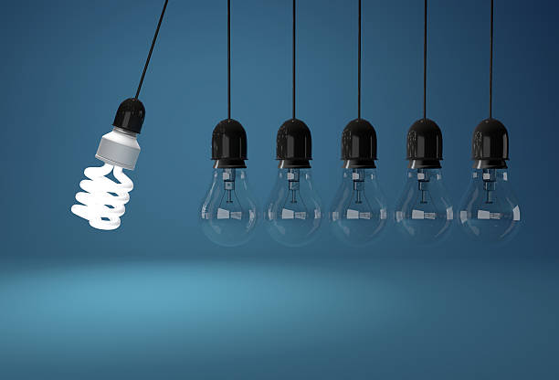 Energy saving and incandescent bulb in perpetual motion over blu stock photo