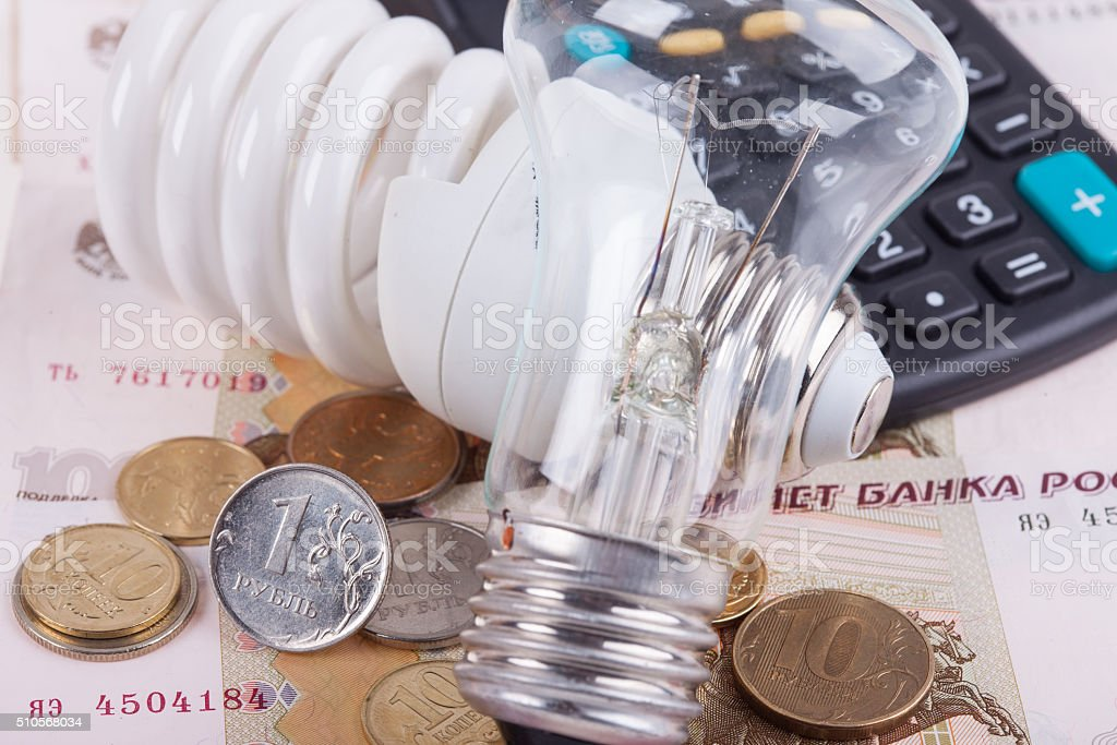 Energy saving concept. Electric light bulb, ruble money and calculator stock photo