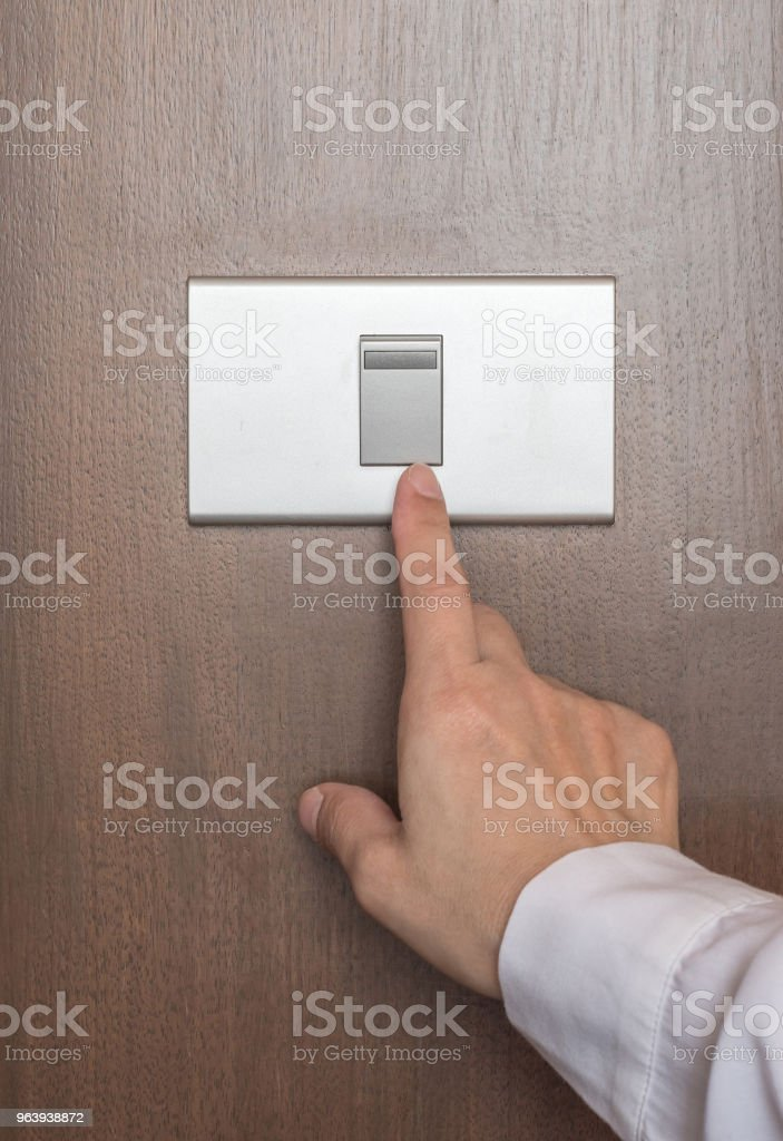 Energy saving concept with business woman's hand turn off switch light button on wood panel - Royalty-free Adult Stock Photo
