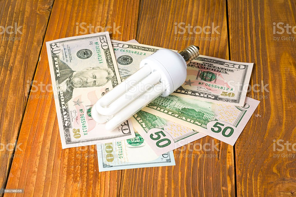 energy saving lamp, incandescent, fluorescent, , electricity, money background, Eco light Стоковые фото Стоковая фотография