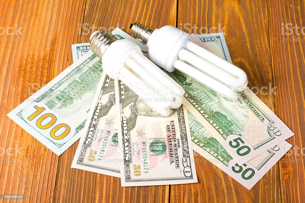 energy saving lamp, incandescent, fluorescent, , electricity, money background, Eco light Стоковые фото Стоковая фотография