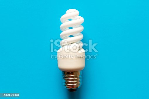 istock Energy saving lamp on blue background. Close up. The concept of energy saving 990833660