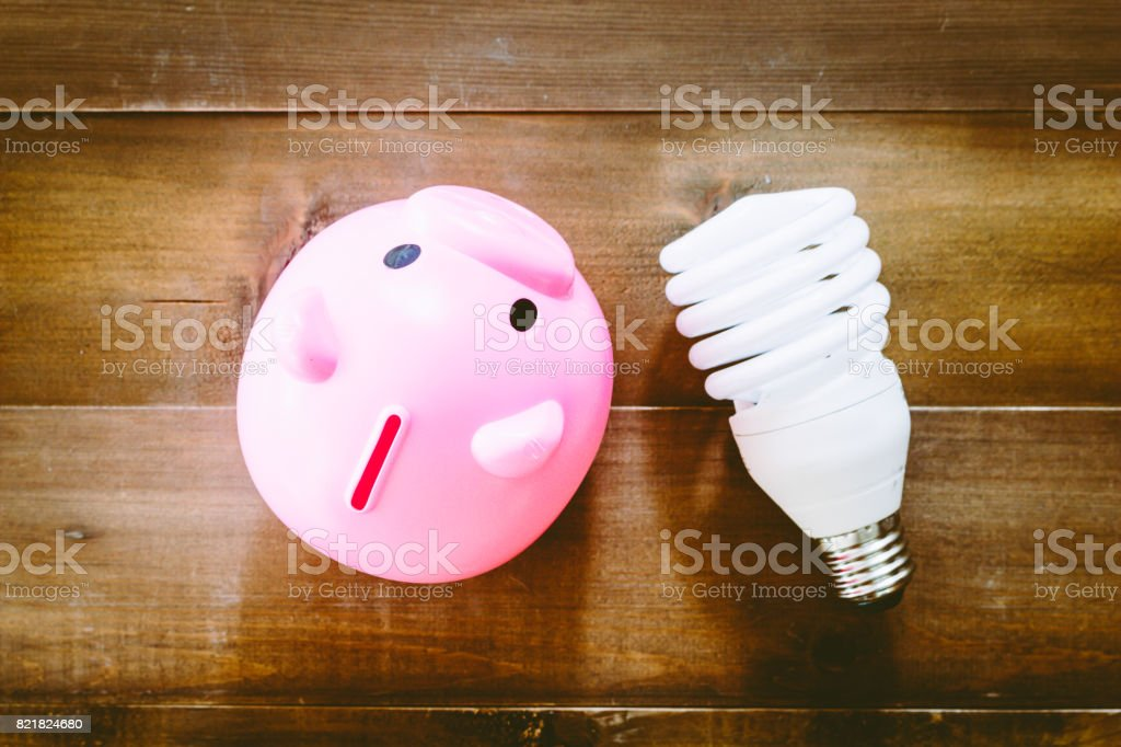 Energy saving lamp with piggy bank on wooden table stock photo