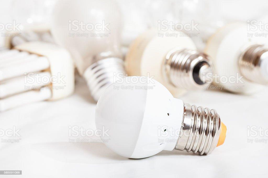 energy saving LED lamp and several old light bulbs stock photo