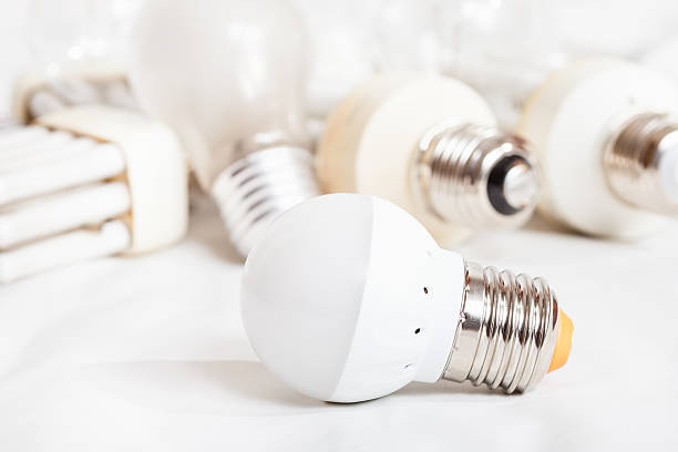 energy saving led lamp and several old light bulbs - glühbirne e27 stock-fotos und bilder
