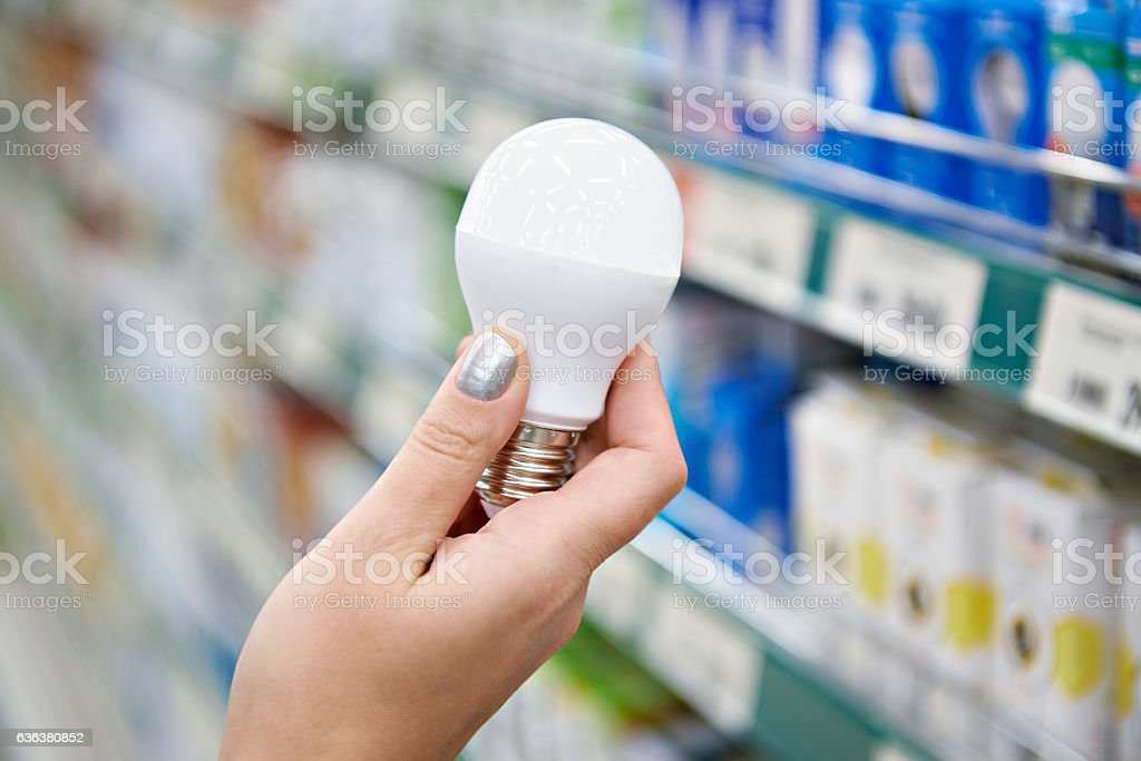 Energy saving LED lamp in hands of buyer at store stock photo
