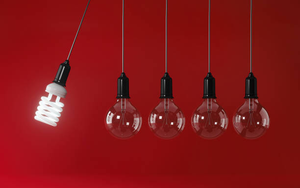Energy Saving Light Bulb In Perpetual Motion on Red Background: Energy Efficiency Concept stock photo