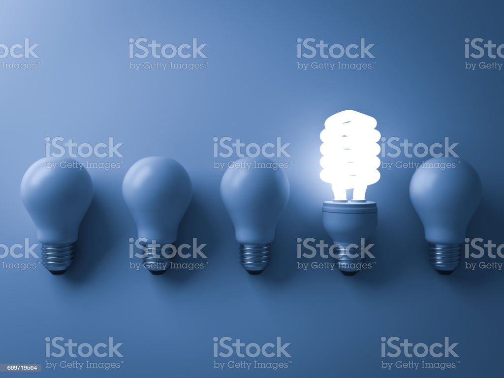 Energy saving light bulb , one glowing compact fluorescent lightbulb standing out from unlit incandescent bulbs on blue background , individuality and different creative idea concepts . 3D rendering stock photo