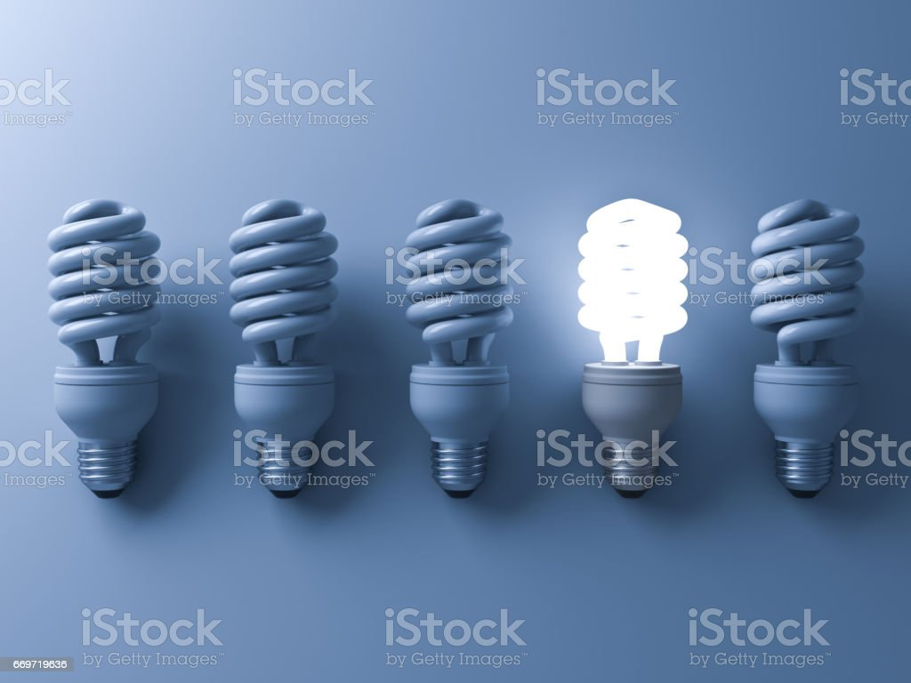 Energy saving light bulb , one glowing compact fluorescent lightbulb standing out from unlit light bulbs on blue background , individuality and different creative idea concepts . 3D rendering stock photo