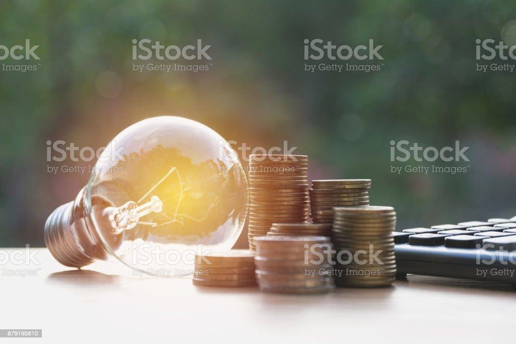 Energiesparlampe mit Stapeln von Münzen und Rechner für Finanz-, Rechnungswesen und speichern Konzept. – Foto
