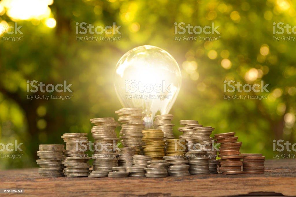 Energy saving light bulb with stacks of coins. stock photo