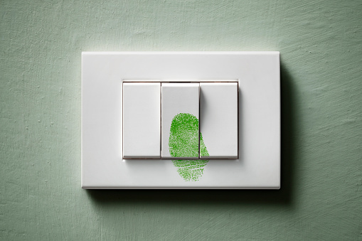 Light switch with green fingerprint.