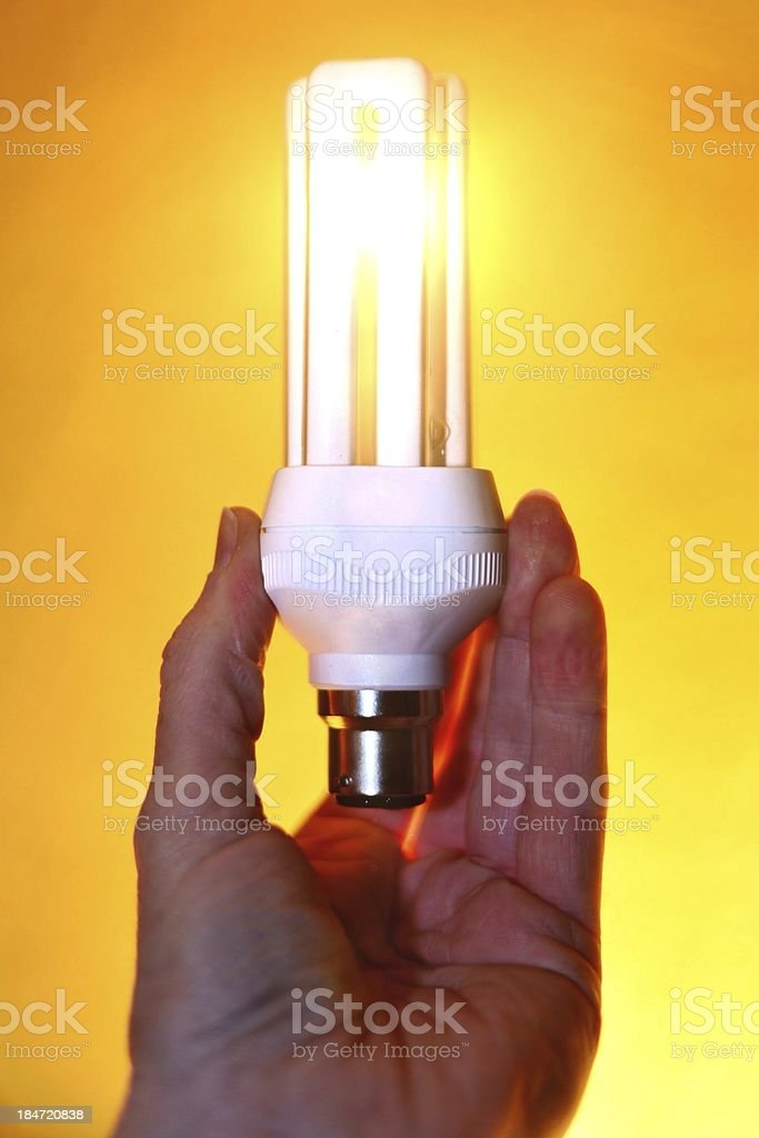 Energy saving lightbulb on yellow background 2 royalty-free stock photo