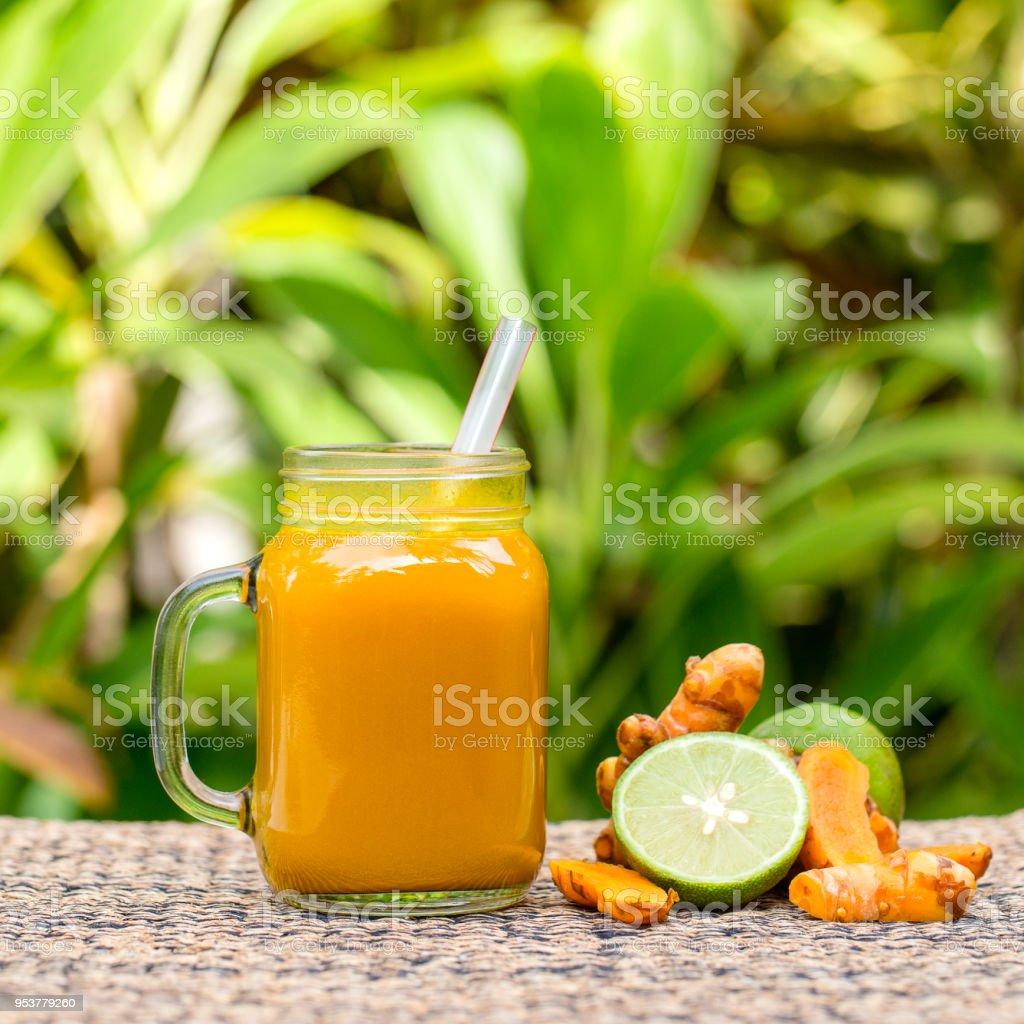 Energy tonic drink with turmeric, ginger, lemon and honey in glass mug, nature background stock photo