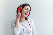 Energy young brunette lady woman listening music in headphones and singing isolated on white background