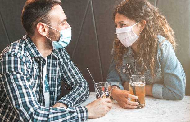Engaged couple sitting in a caffe bar with surgical masks during the coronavirus pandemic - prevention and social distancing concept Engaged couple sitting in a caffe bar with surgical masks during the coronavirus pandemic - prevention and social distancing concept romance stock pictures, royalty-free photos & images