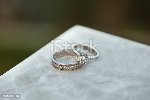 istock Engagement and wedding rings over each other. For Love story . Marble on the stone. 868451210