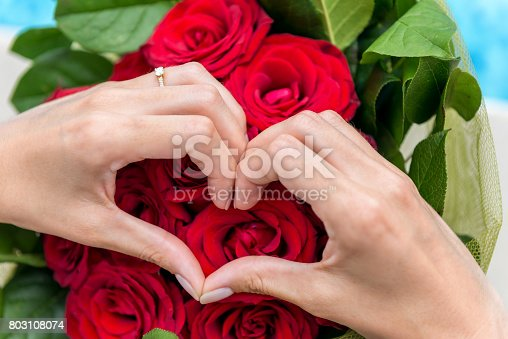 Horizontal color close-up image of woman's hands making a heart shape and wearing diamond gold ring. Bouquet of red roses in the background.