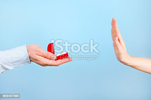 istock Engagement / marriage / wedding proposal refusing / rejection / not accepting scene. Close up of man handing the expensive gold platinum diamond ring to his bride. 909487990