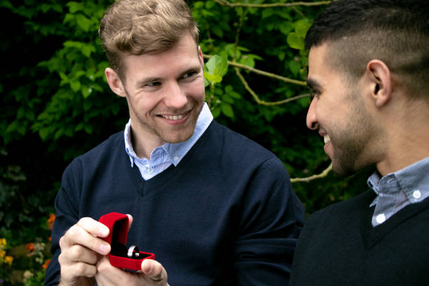 Engagement proposal betwen two gay men as one man proposes with an engagement ring in red box stock photo