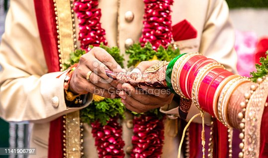Beautiful photo of a ring ceremony being held as per Hindu rituals. Bridegroom is putting a ring to her Bride. Both dressed in traditional hindu marriage attire.