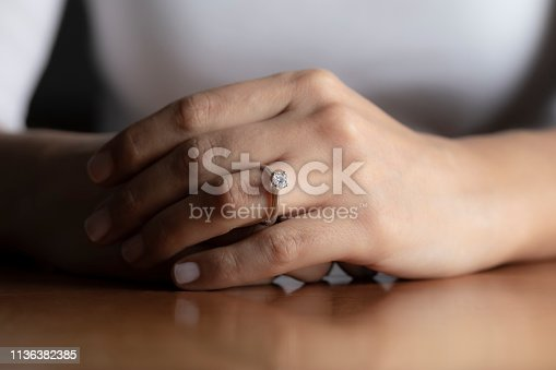 Close up of womans hand wearing an engagement ring.