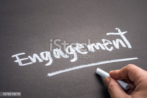 Hand writing the word ENGAGEMENT on chalkboard