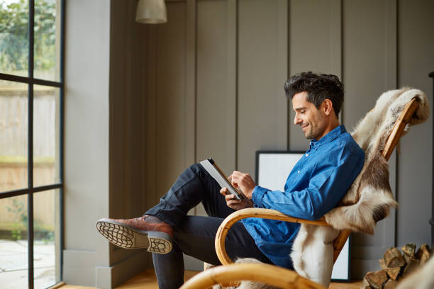 Engaging with the world online Shot of a young man using a digital tablet while relaxing on a rocking chair at home bachelor stock pictures, royalty-free photos & images