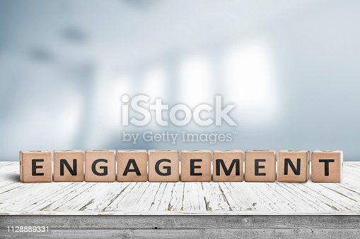 Engagment sign made of wooden blocks on a table in bright room with windows