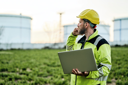 Male engineer using a laptop and talking on phone in front of oil refinery. Engineering concept