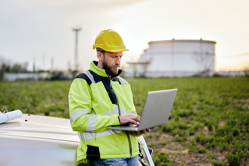 Male engineer using a laptop and blueprints in front of oil rafinery. Engineering concept.