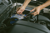 istock Engine engineer is replacing  car battery because car battery is depleted. concept car maintenance And the cost of car care. 1280716416
