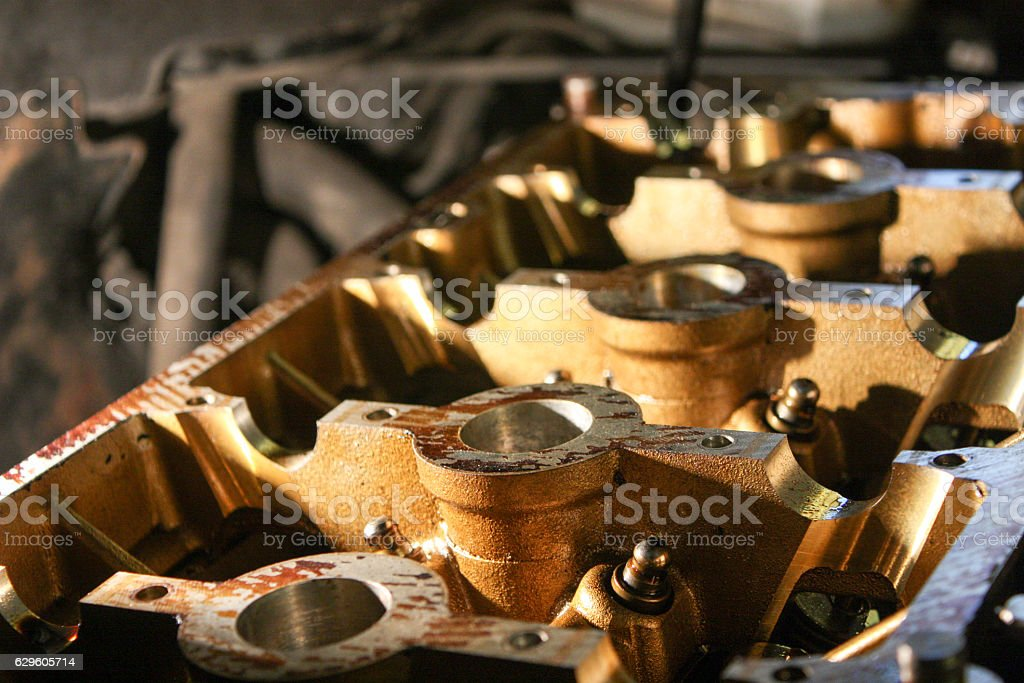 Engine of four cylinder petrol engine. Head in the workshop. stock photo