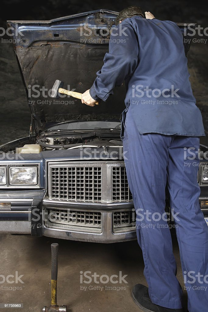 Engine repair with hammer royalty-free stock photo