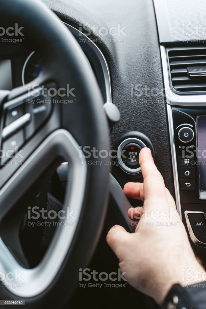 Engine start button and finger with shallow depth of field stock photo
