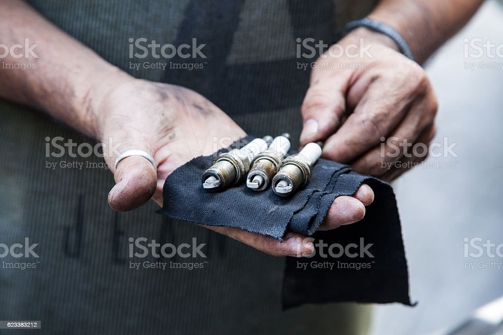 Engine technician changing spark plug - foto de stock