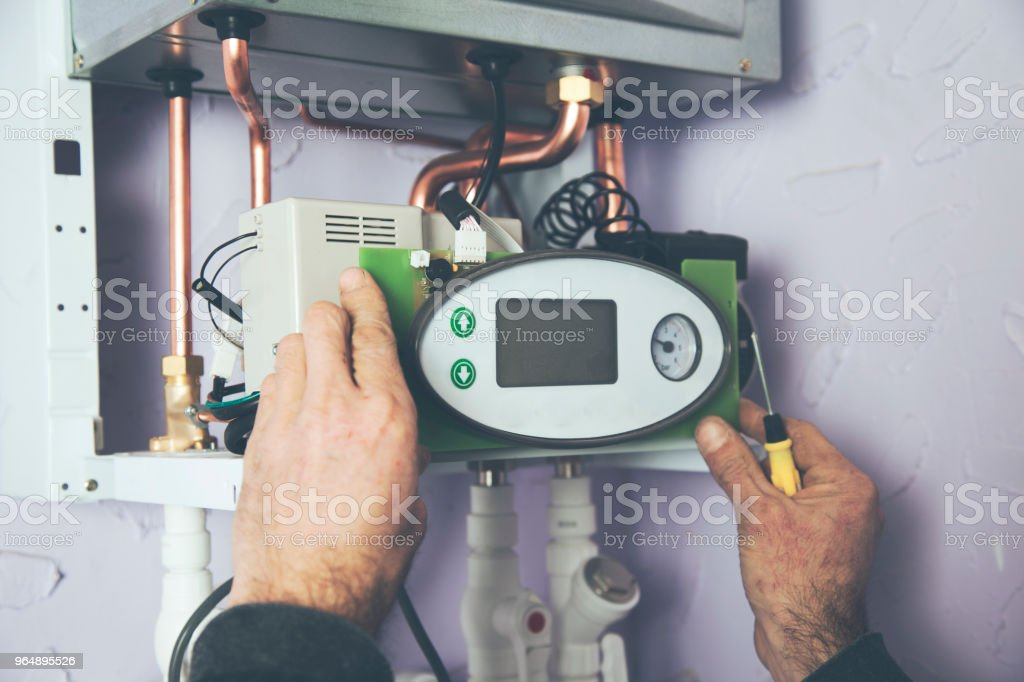 Engineer adjusting thermostat for efficient automated heating system royalty-free stock photo