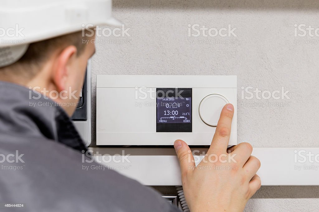 Engineer adjusting thermostat stock photo