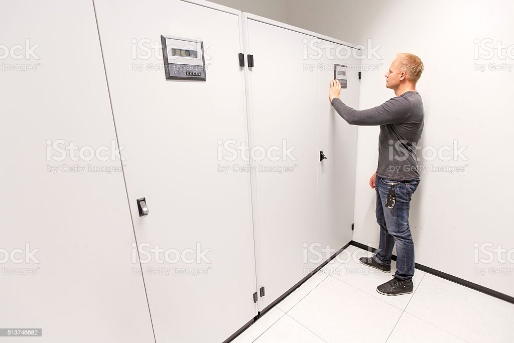 IT engineer adjusts air conditioner in datacenter stock photo