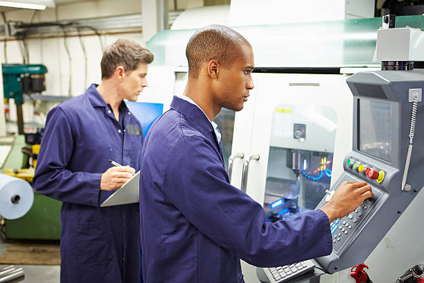 Engineer And Apprentice Using Automated Milling Machine stock photo