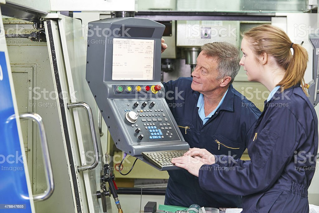 Engineer And Apprentice Using Computerized Cutting Machine stock photo
