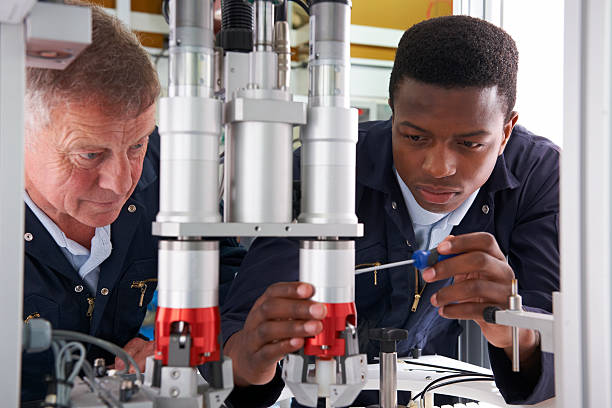 Engineer And Apprentice Working On Machine In Factory stock photo